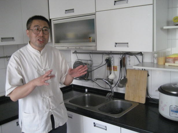 "Huang He shows off the model ""kitchen"" where migrant trainees learn how to cook."